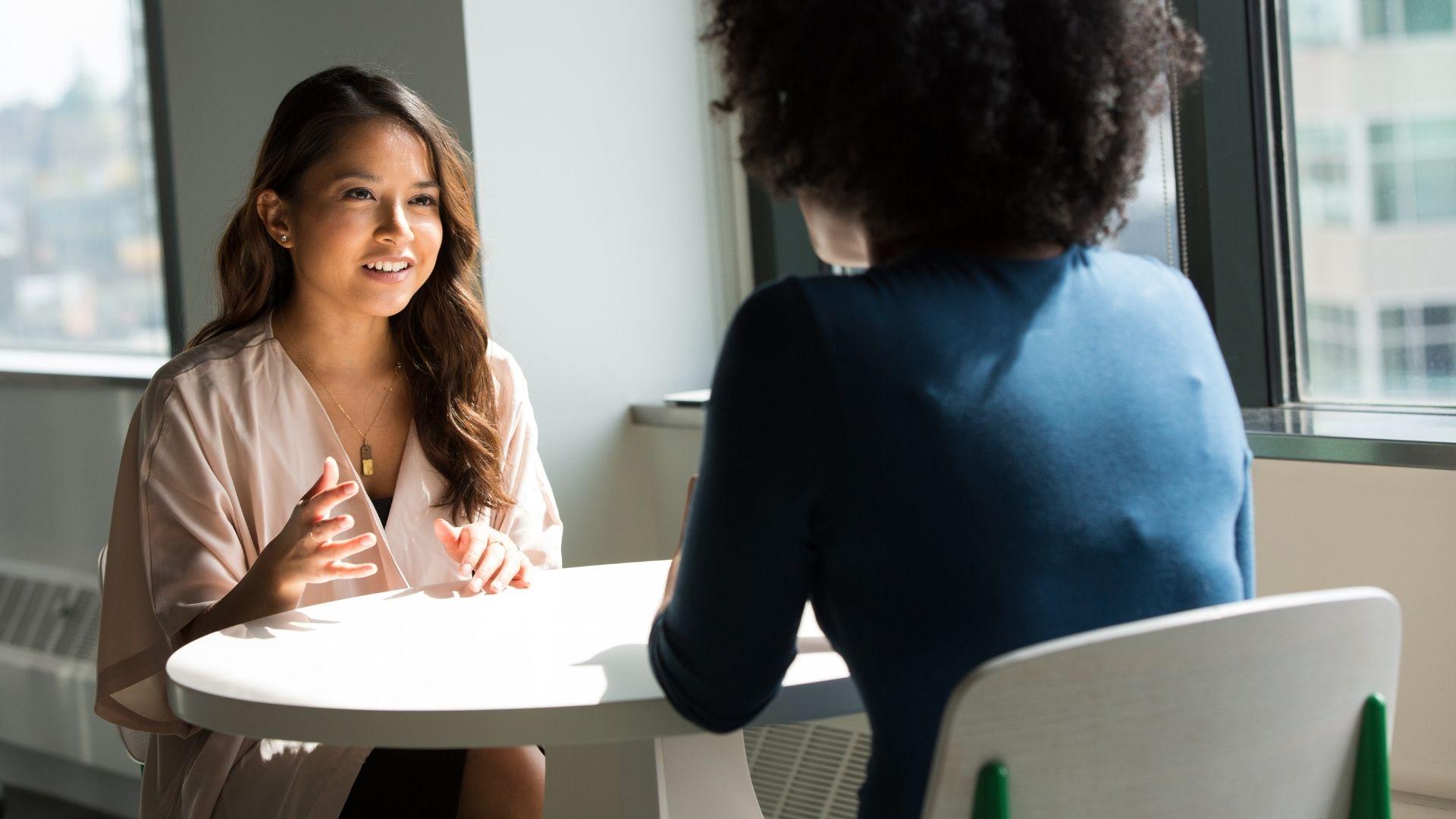 Zwei Frauen fröhliches Gespräch am Tisch