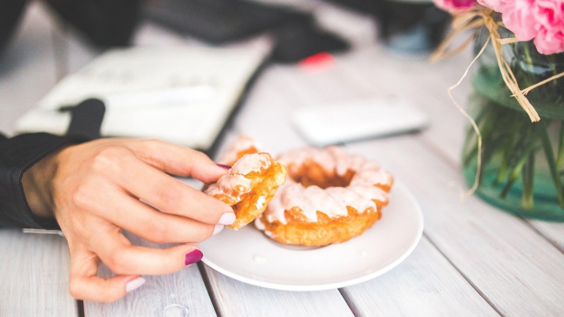 weibliche Hand greift nach Spritzkuchen